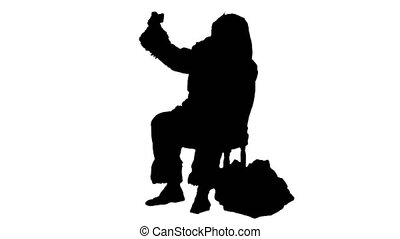 Silhouette Santa makes selfie with smartphone. Professional...
