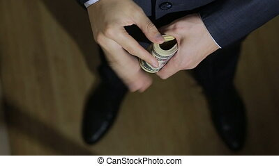 Male businessman finds a wad of money, dollars. view from...