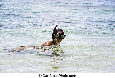 Girl swims in the sea snorkelling