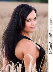 A beautiful woman with black haired amid wheat field