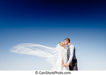 newly married couple.wind lifting long white bridal veil...