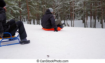 Young falimy riding down a steep hill on a sled. winter park