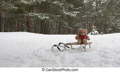 Toy bear laying down on the sled in winter