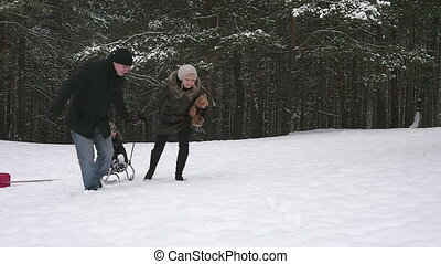 Parents running with their child on a sled in the winter...