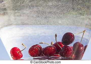 red cherries in water - red ripe juicy cherries in clear...