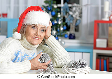 Senior woman with Christmas decorations - Portrait of...