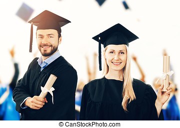 happy graduates with diplomas wearing gowns at graduation ceremony