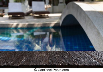 bridge across swimming pool with wood table for display your...