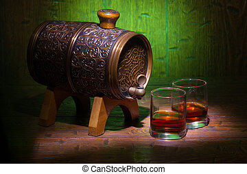 Glasses of whiskey and small barrel on wooden table -...