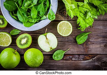 green vegetables: kiwi, spinach, apple, lime, celery on a...