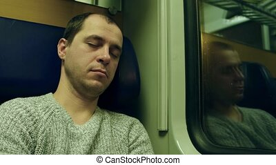 Man in sweater sleeping in his seat in a train. 4K video -...