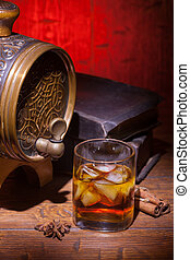 Glasses of whiskey, spicery, books and small barrel -...