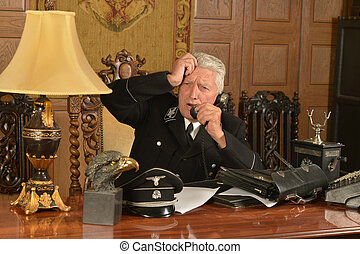 Military mature general calls on the phone in his office