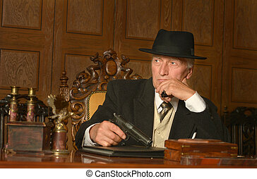 Mature male mafia boss on the table with gun
