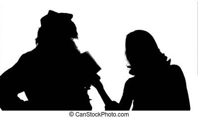 Silhouette Happy Santa Claus with his woman helper reading Christmas letter or wish list