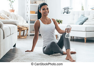 Good work! Attractive young woman smiling and looking at camera while sitting on the carpet at home