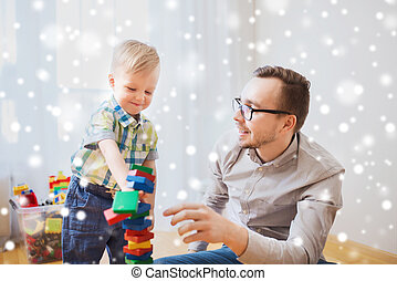 father and son playing with toy blocks at home - family,...