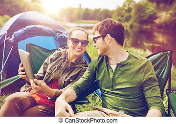 happy couple with tablet pc at camping tent - travel,...