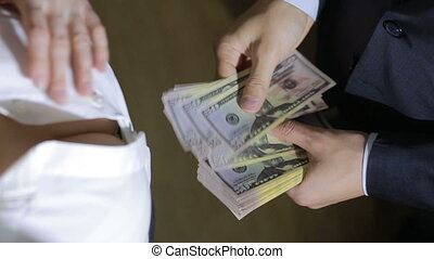 Beautiful young slim girl counts the money transferred to her man