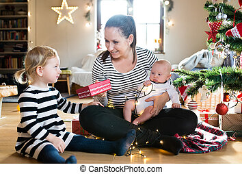 Mother giving daughter Christmas present, holding her son. -...