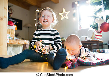 Boy and girl under Christmas tree entangled in chain of...
