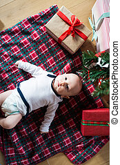 Little baby boy lying under Christmas tree among presents -...