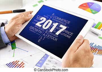 man with tag cloud of goals for 2017 in tablet - a young...