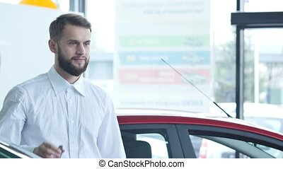 Man standing while holding car keys in a dealership.