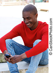 smiling black man sitting outside using cellphone