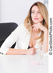 Beautiful businesswoman sitting in office - Beautiful young...