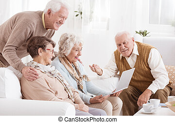 Group of seniors with laptop - Group of seniors watching...
