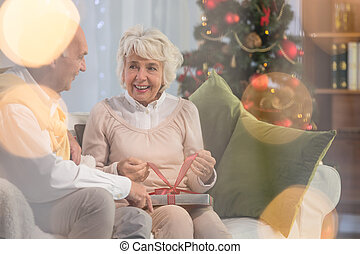 Senior woman receiving gift from husband