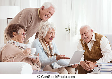 Elderly people using computer, sitting in light room