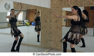 Beautiful woman dances belly dance in studio with many mirrors.