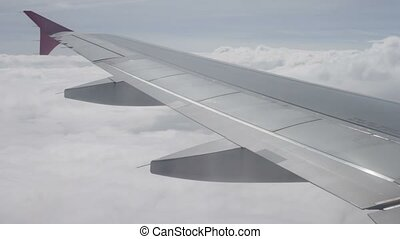 Wing of airplane flying above the clouds in sky - Blue sky...