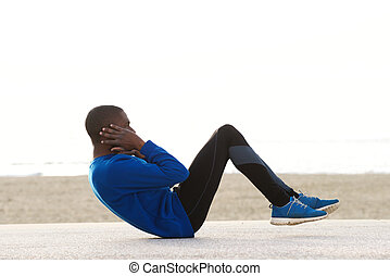 young black man exercising on the beach doing sit ups