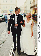 Happy newlyweds walk along the tramways in the old city