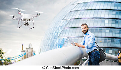Hovering drone taking pictures of man against Town Hall in Londo