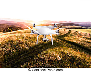 Hovering drone taking pictures of green nature at sunset -...