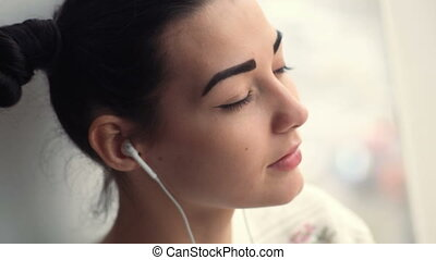 Charming young woman in earphones sitting near window listening musik