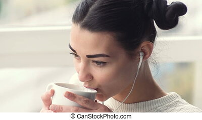 Charming young woman in earphones sitting near window...