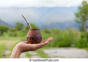 Yerba mate in a traditional calabash gourd, hand, space for...