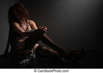 Sexy woman sitting in corner with chains