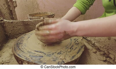 Potter's wheel. Women's hands are trying to make Pot....