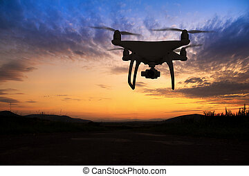 Silhouette of hovering drone taking pictures of nature at...