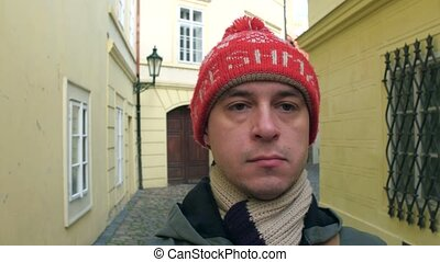 Sad man in red knitted hat walking on a narrow old town street in Prague. 4K steadicam video