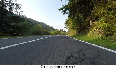 Speeding down side camera on a beautiful road through...