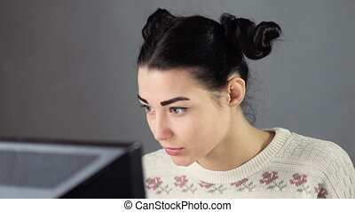 Surprised young woman surfing internet at home - Restricted...