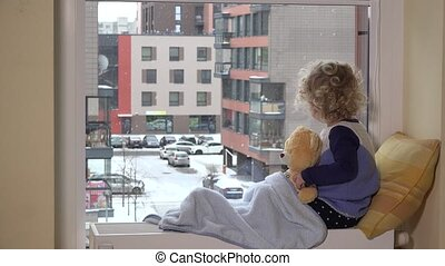 Sad toddler boy with best friend teddy bear looking at snow fall through window