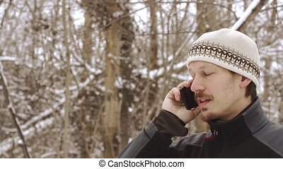 Adult serious man talking on the phone outdoors in winter HD